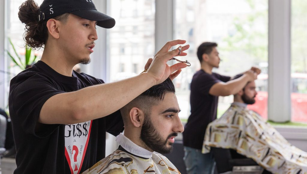 Pivot Point barber cuts a client's hair