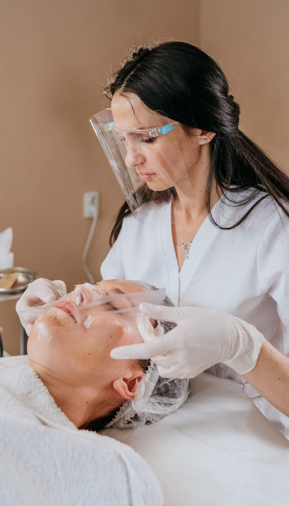 Beauty specialist doing facial treatment for female customer