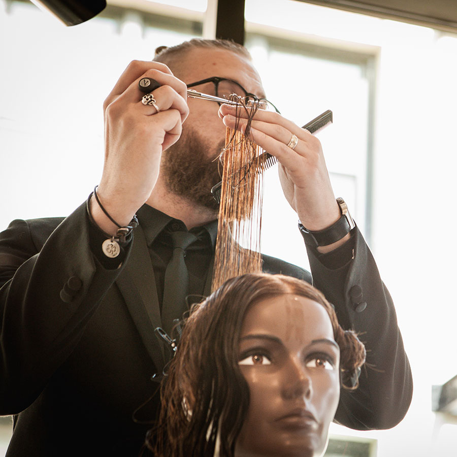 Pivot Point instructor demonstrating hair cutting techniques