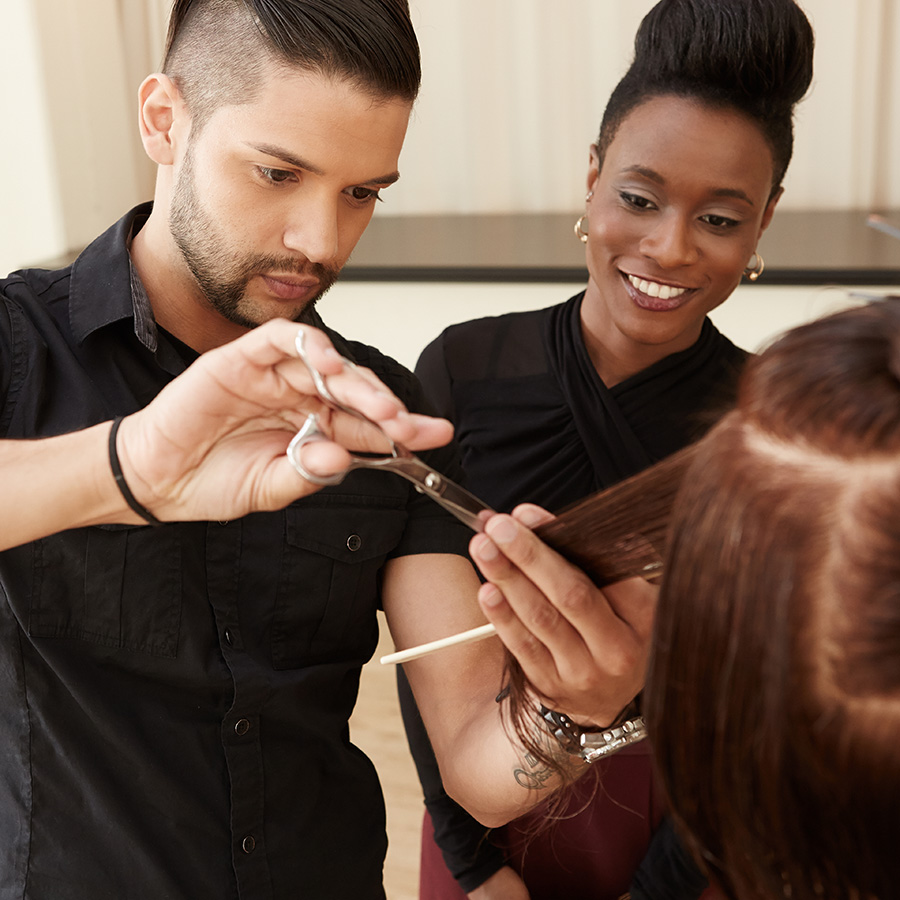 Pivot Point instructor guiding students in haircut training