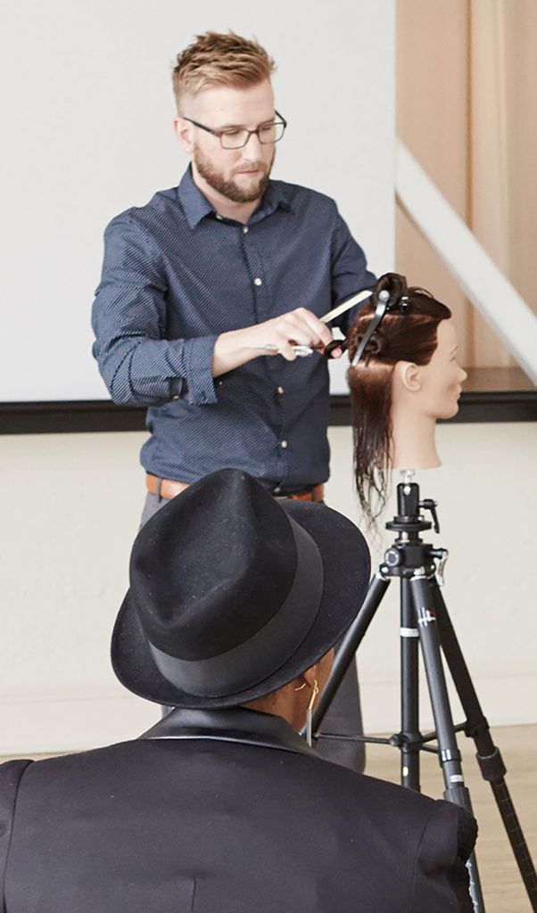 Pivot Point instructor showing students hairstyling techniques while another instructor recording with an ipad