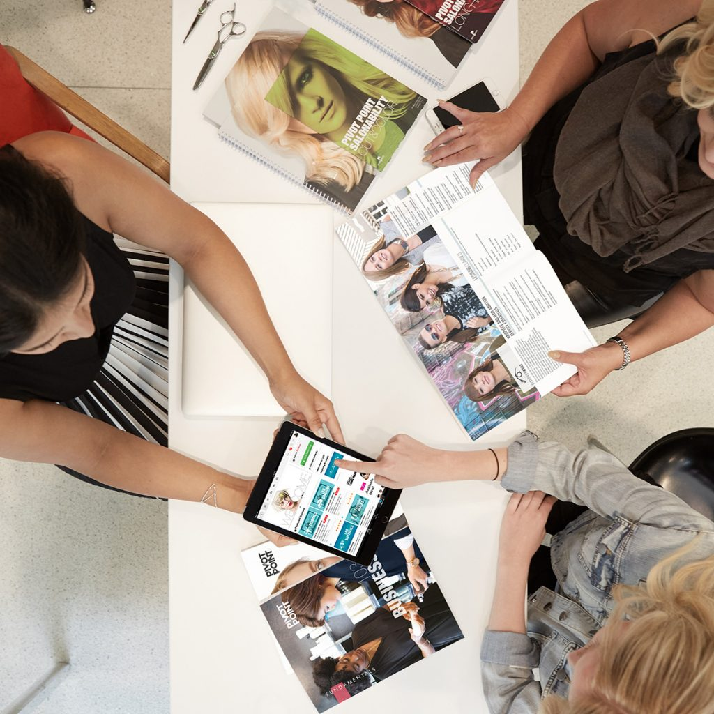 Pivot Point students checking Pivot Point booklets, brochure and Lab on ipad