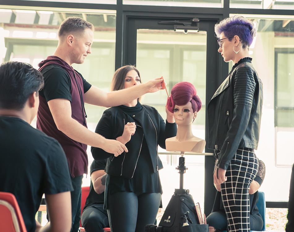 Pivot Point instructors showing students hairstyling techniques