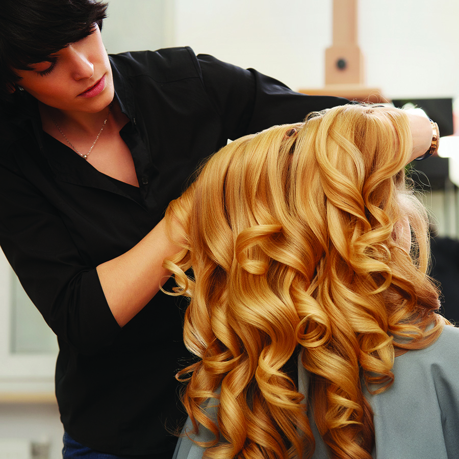 Blonde curly hair. Hairdresser doing hairstyle for young woman in salon