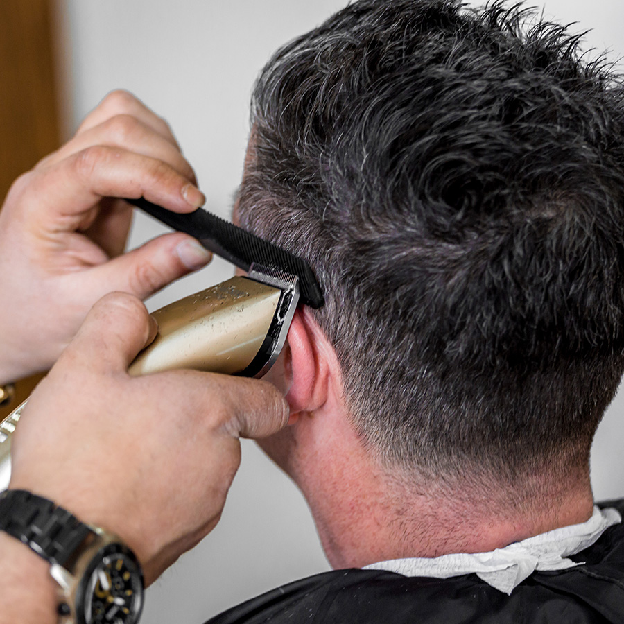 Close up of trimming hair with electric trimmer