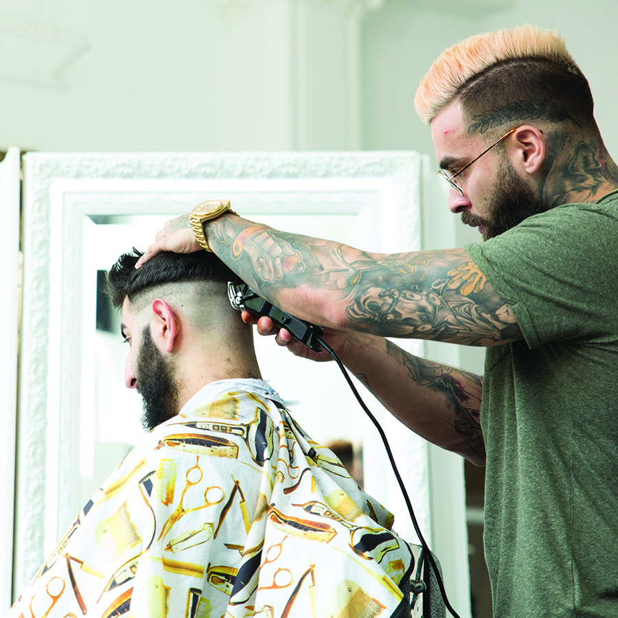 Barber trimming hair for male customer