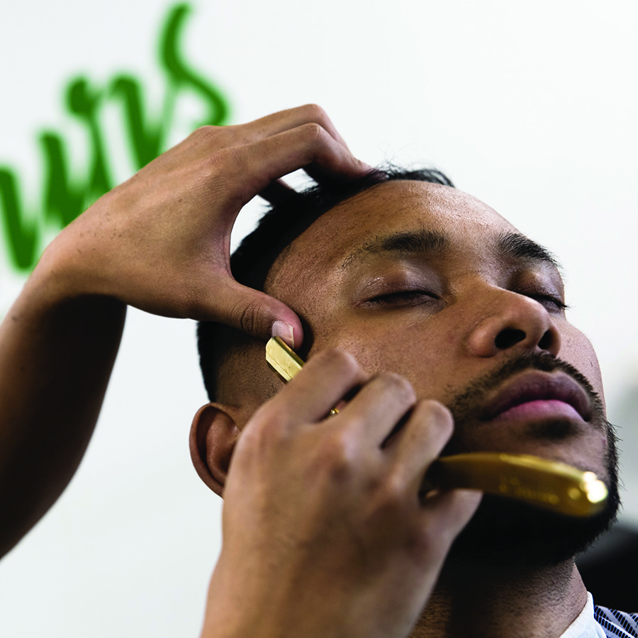 Close up of shaving hair with male customer