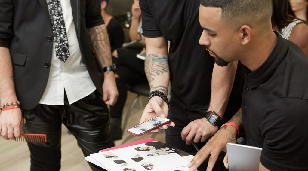 Pivot Point instructor showing students how to watch trend workshops by scanning codes on trend books