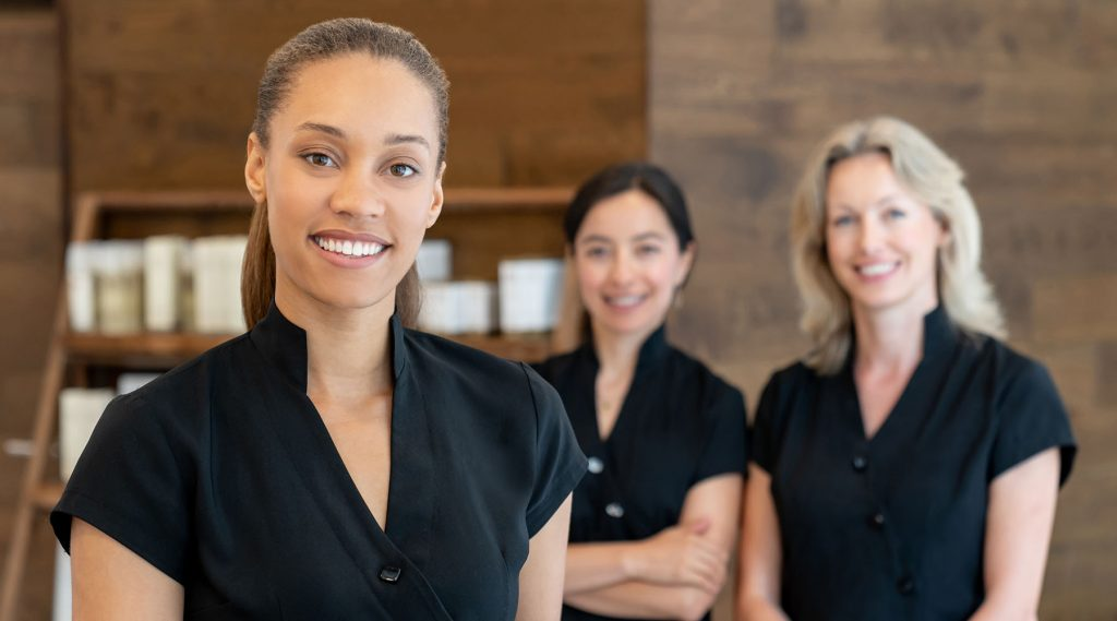 Portrait of a group of women working at a spa and looking at the camera smiling - beauty concepts