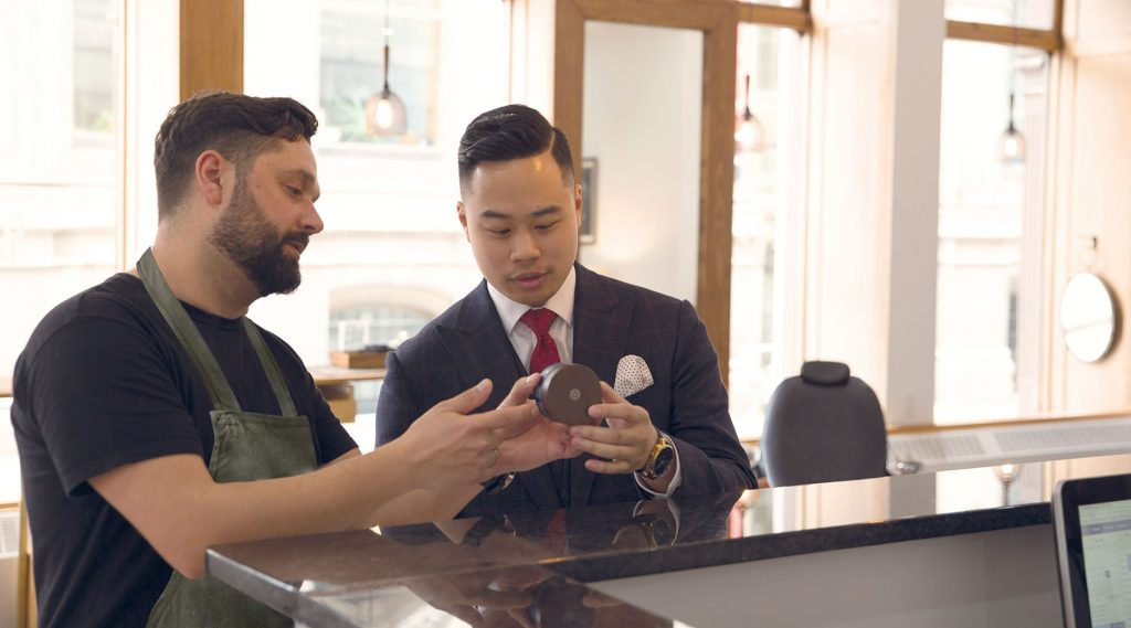 Barber showing client product in a modern store