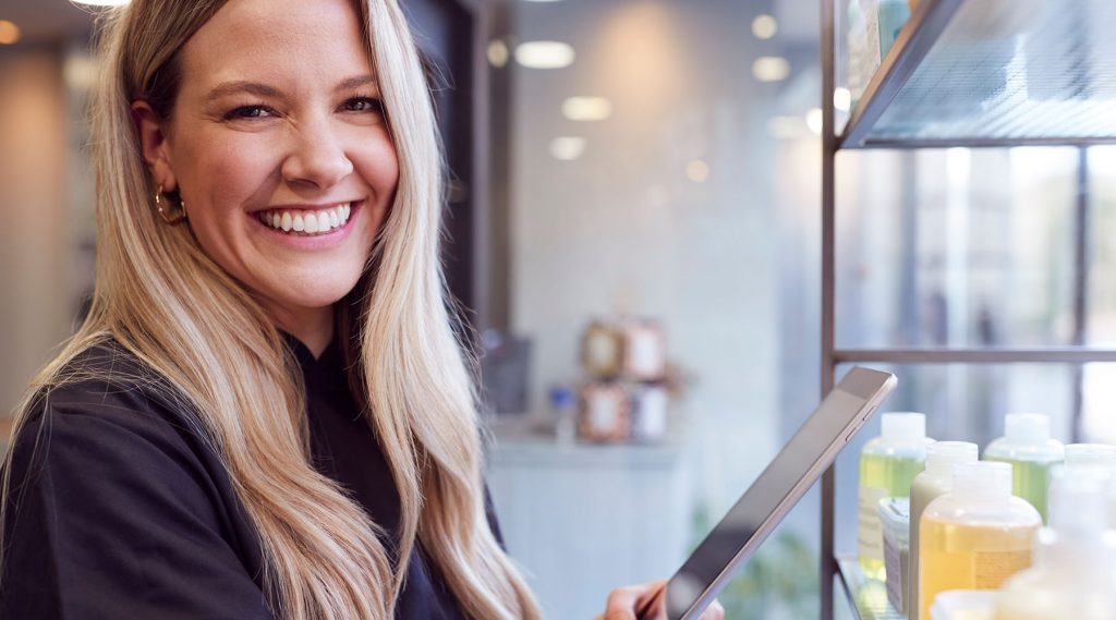 Product manager facing camera with smile and holding an ipad