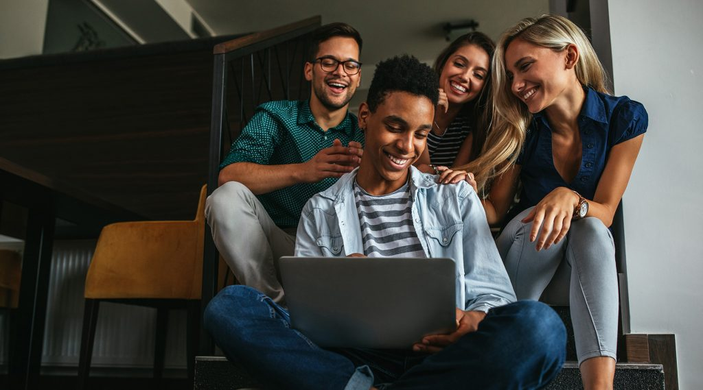 Person on computer being congratulated by friends.