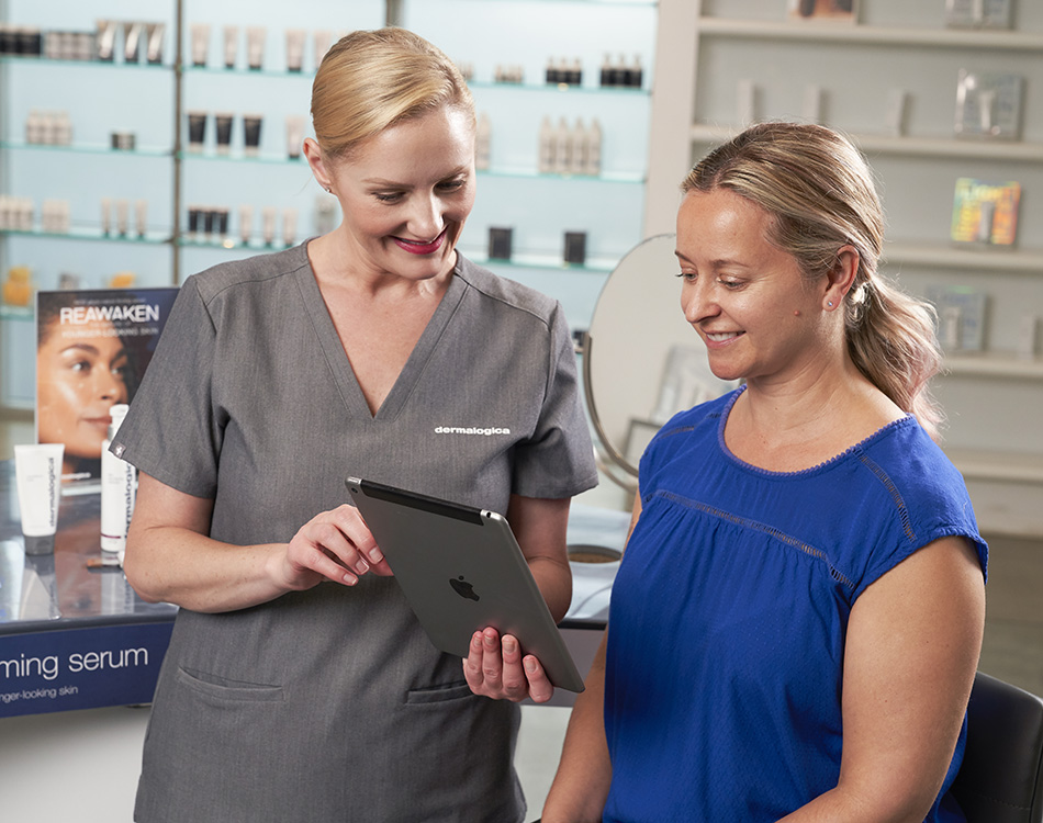 Dermalogica Esthetician working with a client on tablet